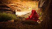 foto of female buffalo  - Indian villager women making cow dung cake sitting in red saree - JPG