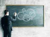 pic of mechanical drawing  - businessman drawing gears on a chalk board - JPG