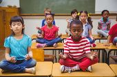 picture of pupils  - Pupils meditating in lotus position on desk in classroom at the elementary school - JPG