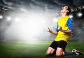 pic of kneeling  - soccer or football player is celebrating goal on stadium - JPG