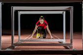 stock photo of sprinter  - Young athlete on the starting block in hurdles race - JPG