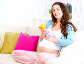stock photo of expectations  - Pregnant Happy Woman sitting on a sofa and eating apple - JPG