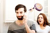 pic of breakup  - Young rage woman hitting her talking partner with frying pan - JPG