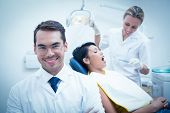 picture of dentist  - Portrait of smiling male dentist with assistant examining womans teeth in the dentists chair - JPG