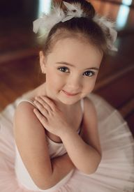 pic of ballerina  - Portrait of a cute little ballerina in a white suit and with feathers in her hair  - JPG