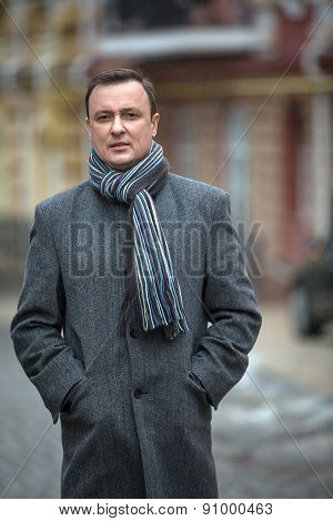 Stylish man in a gray coat with scraft on the street