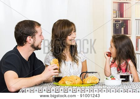 Cute family with little girl eating breakfast