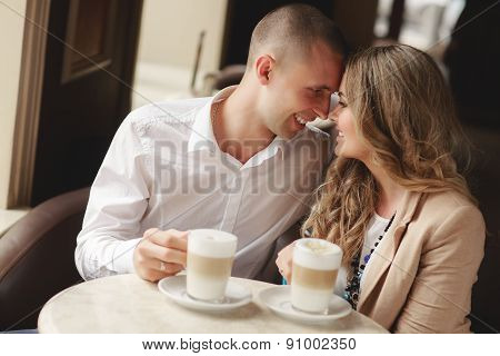 Happy couple drinking coffee in an urban café.