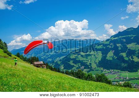 Paraglider preparing for flight on alpine meadows