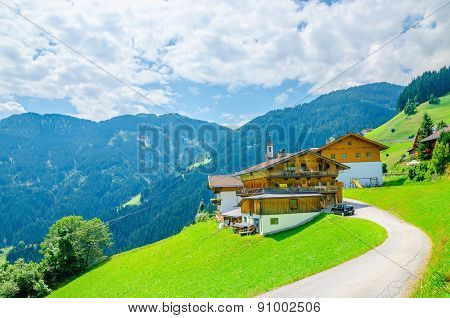 Alpine building with green meadows and high peaks