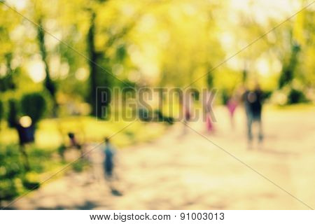 Natural bokeh background of people walking in park. Intentional motion blur.