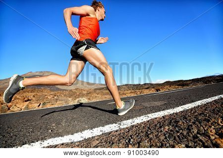 Runner man running sprinting for success on run. Male athlete runner training at fast speed. Muscular fit sport model sprinter exercising sprint on mountain road. Full body length of Caucasian model.