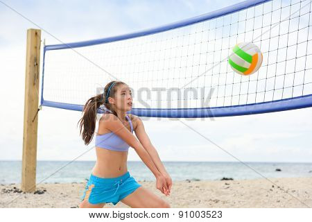 Beach volleyball woman playing game hitting forearm pass volley ball during match on summer beach. Female model living healthy active lifestyle doing sport on beach.