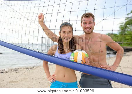 Beach volleyball portrait of people, woman and man looking at camera smiling after playing having fun in summer. Young woman and man fitness model living healthy lifestyle doing sport on beach.