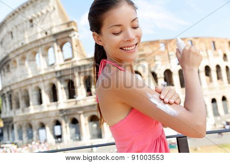 Woman applying sunscreen suntan lotion on travel in Rome by the Colosseum. Beautiful happy woman Asian putting solar cream from a plastic container in Italy while enjoying Europe summer traveling.