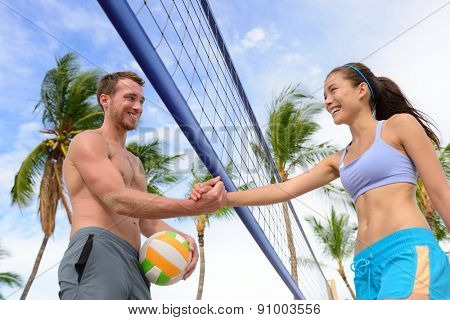 Handshake people in beach volleyball shaking hands after volley ball game on summer beach. Man and woman model living healthy active fitness lifestyle doing sport on beach.