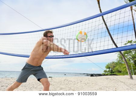 Beach volleyball man playing forearm pass hitting volley ball during game on summer beach. Male model living healthy active lifestyle doing sport on beach.