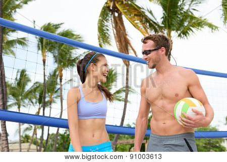Beach volleyball. People playing having fun in sporty active lifestyle portrait holding volley ball after game in summer. Woman and man fitness model living healthy lifestyle doing sport on beach.