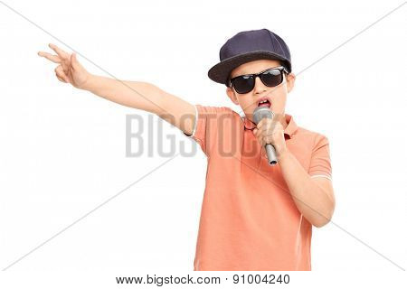 Little boy in hip hop outfit rapping on a microphone and gesturing with his hand isolated on white background