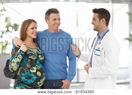 Young and cheerful pregnant couple talking to doctor at clinic. Husband and wife embrace each other.