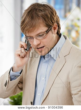 Young caucasian businessman talking on mobile phone, suit with no tie, wearing glasses, looking down, goatee.