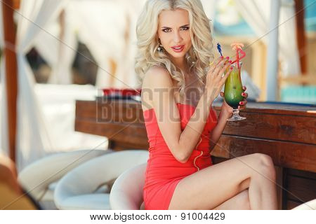 Portrait of a girl with a cocktail at the beach bar.