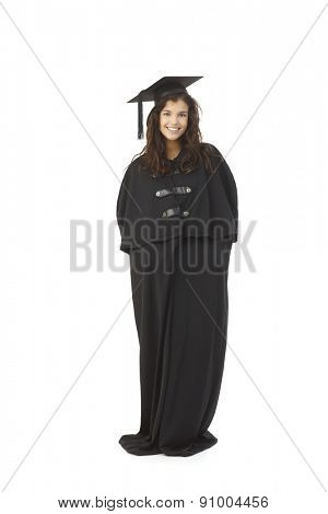 Happy female graduate standing in full academic dress, smiling.