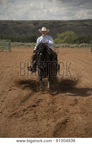 Cowboy Running Toward On A Black Horse