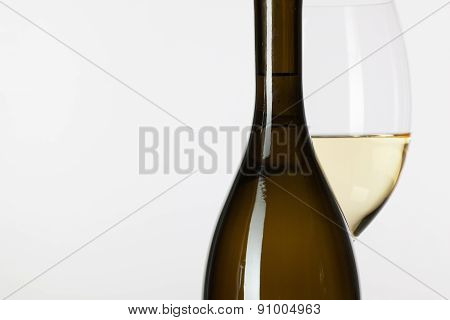 Glass Of White Wine And Brown Bottle