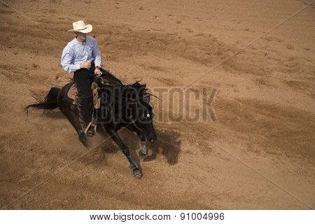 Top View Of A Cowboy Sliding To A Stop On A Black Horse