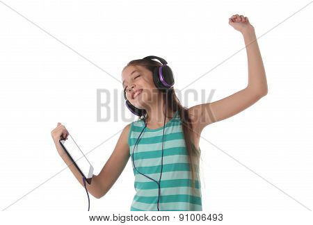 Beautiful pre-teen girl dancing with a tablet and headphones.