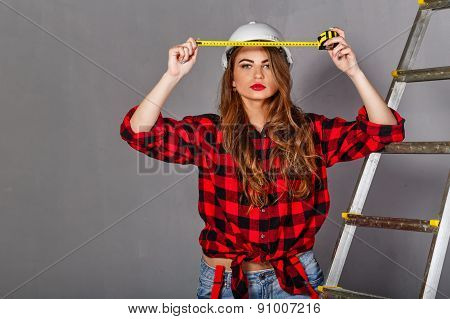 Woman Builder Holds Tape Measure