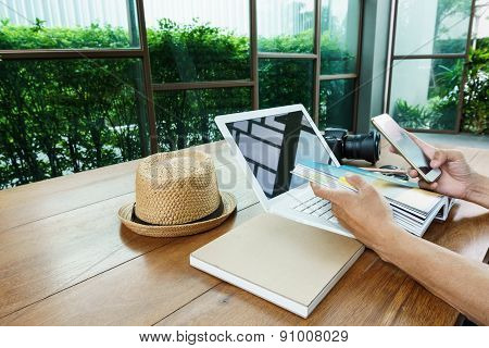 Using Mobile Phone And Laptop On Wood Table
