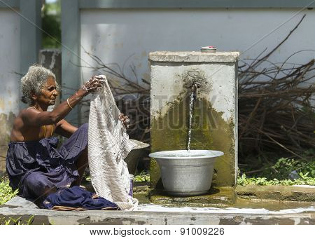 Old Woman Does Laundry At The Communal Pump.