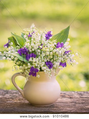 Beautiful bouquet of lilies of the valley and violets on the table