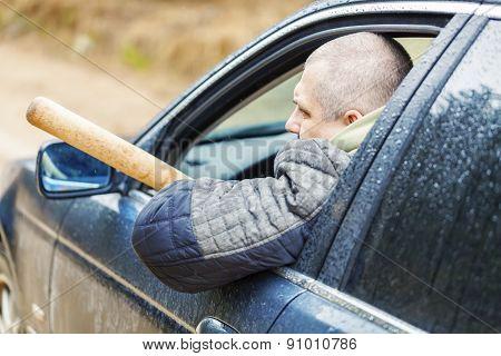 Aggressive man with a baseball bat in car