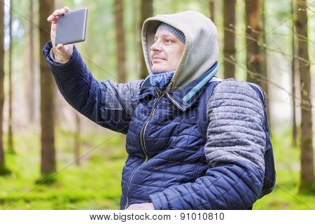 Hiker filmed with tablet PC in forest