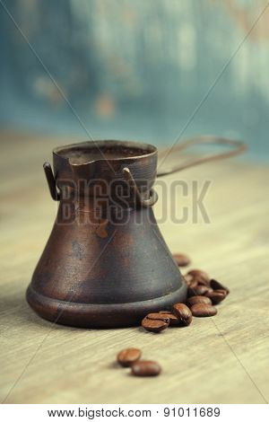 Old coffee pot on blue rustic background