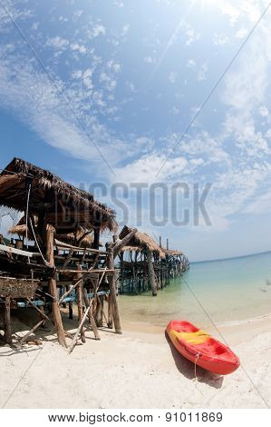 Canoe On The Beach And Traditional Wooden Bridge.