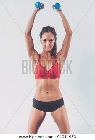 Portrait of athletic woman pumping muscles doing workout lifting up dumbbell exercise for shoulders