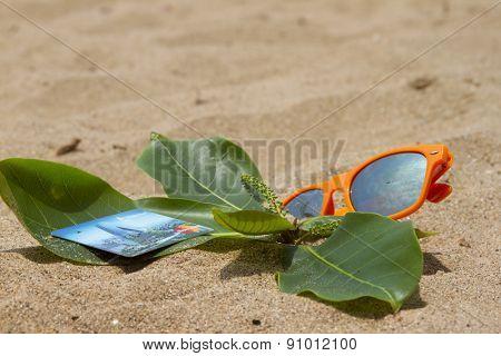 Orange sunglasses and bank cards lying on the sand beach. India Goa.