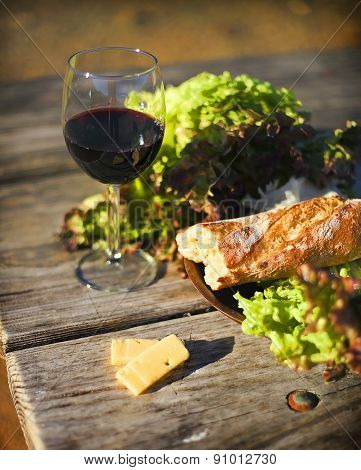 Wine, bread, letuce and cheese on the wooden table