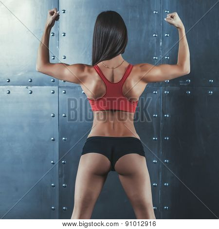 Muscular active athletic young woman with sexy buttocks showing muscles of the back shoulders and ha