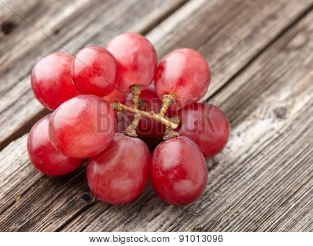 Red grapes on a wooden background