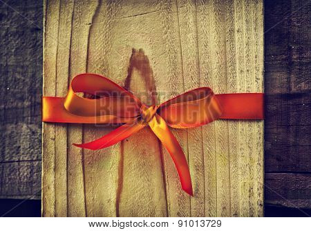 Red silk ribbon Bow on wooden board as copy space