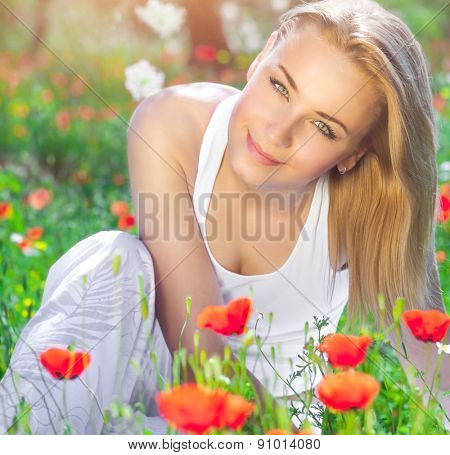 Beautiful young girl sitting on fresh poppy flower field, having fun in fresh floral garden, enjoying amazing spring time sunny day