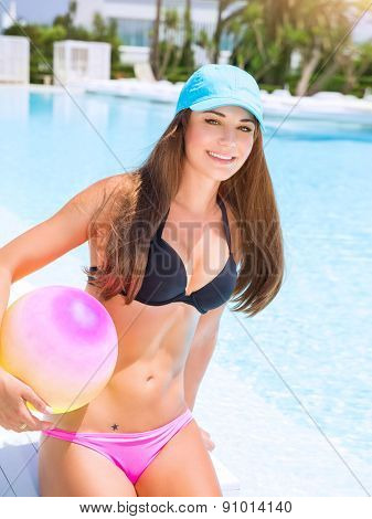 Sexy sportive girl having fun in swimming pool  with ball, enjoying luxury beach resort, active summer vacation, sport and enjoyment concept