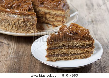 Piece Of Cake With Honey Shortcakes And Sprinkle With Nuts On A White Plate.