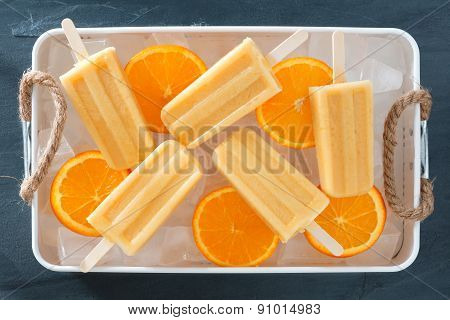 Homemade orange popsicles in a rustic ice tray