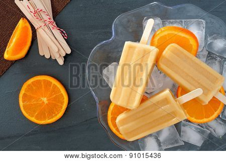 Orange yogurt popsicles in an ice filled bowl
